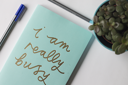 Photograph of a blue notebook with gold text on top that says 'I am very busy'